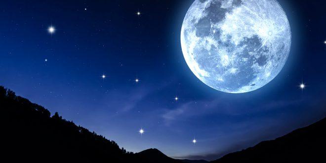 Ein überdimensional großer Mond steht über einer Landschaft.