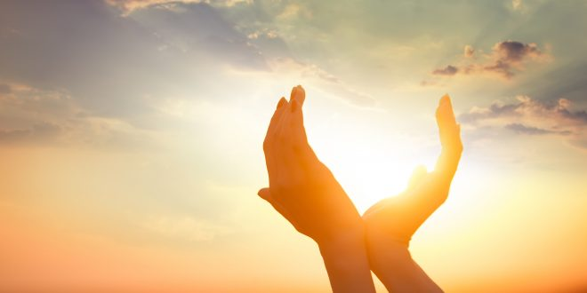 Hände strecken sich gen Himmel und halten die Sonne.