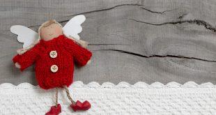 Kleiner roter Engel auf einem Holzhintergrund